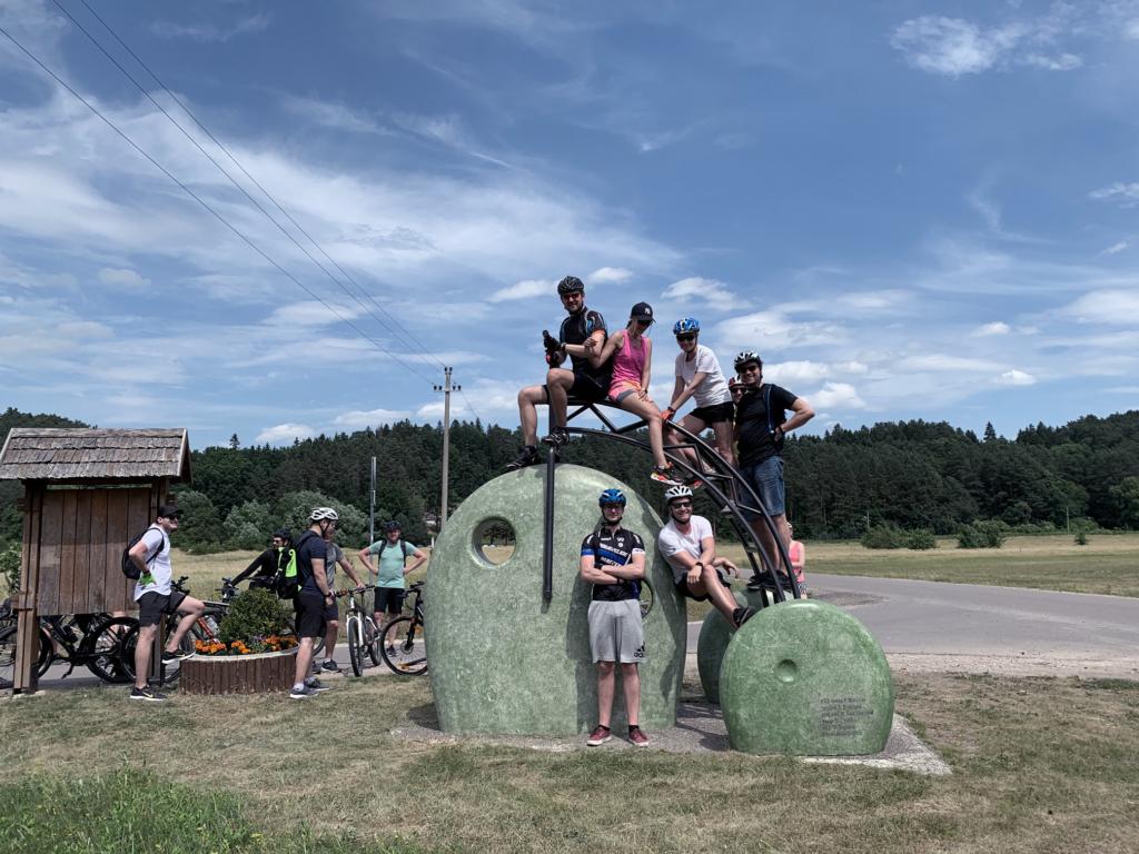 Žmonės susėdę ant dviračio skulptūros