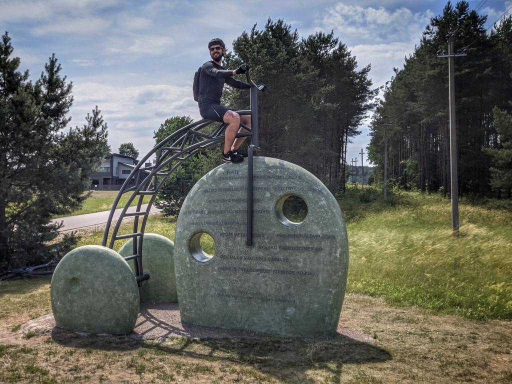 Akmeninė dviračio skulptūra ir ant jos sėdintis žmogus